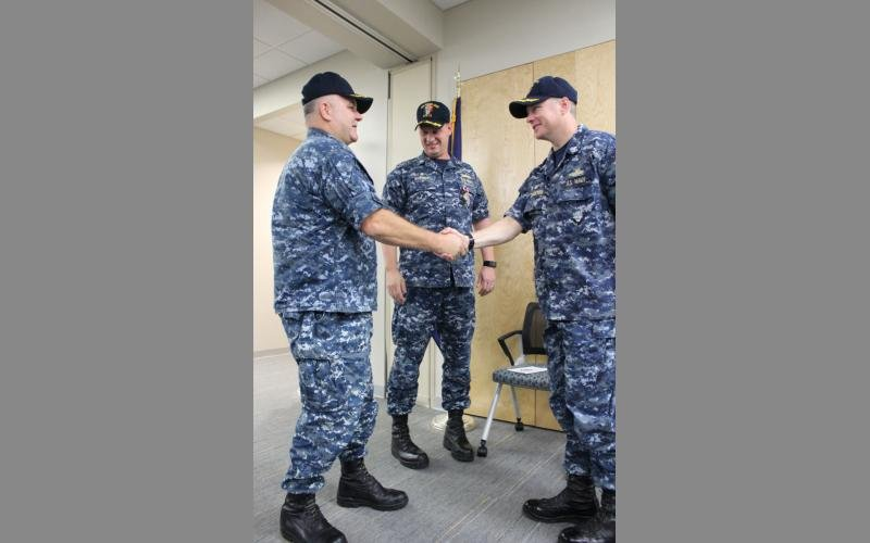 "Cmdr. James ""Randy"" Malone, left, shakes hands with Capt. Michael Johnston, after relieving Cmdr. William S. Snyder, middle, as the USS Sioux City's commanding officer."
