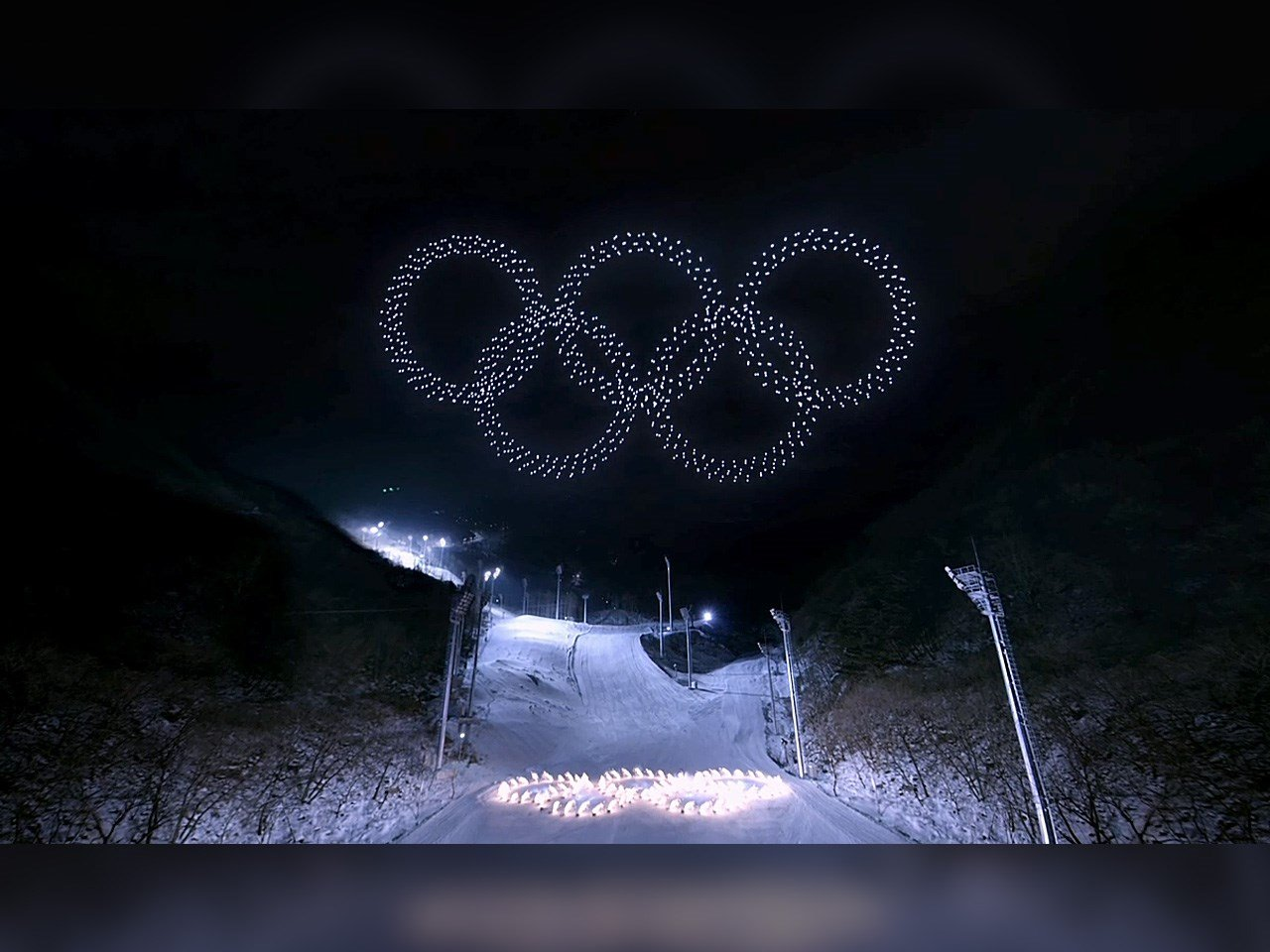 018 Winter Olympics Opening Ceremony in PyeongChang South Korea. Drones creating the Olympic rings in the air as skiers create them on the ground.