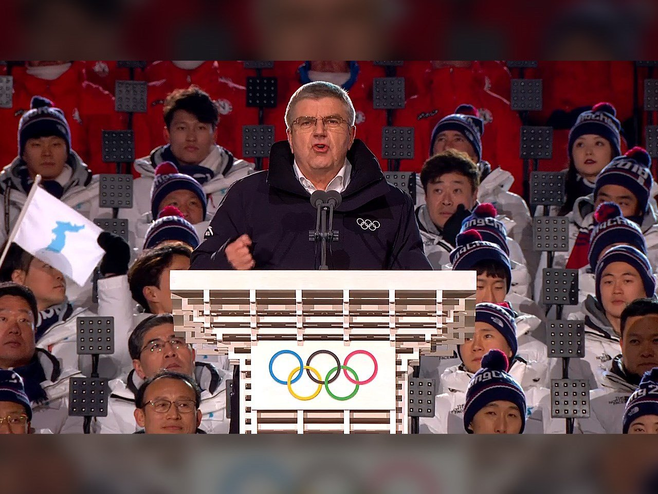 Thomas Bach - President of the International Olympic Committee speaking at the 2018 Winter Olympics Opening Ceremony in PyeongChang South Korea. Behind him is the Unified Korean Team.