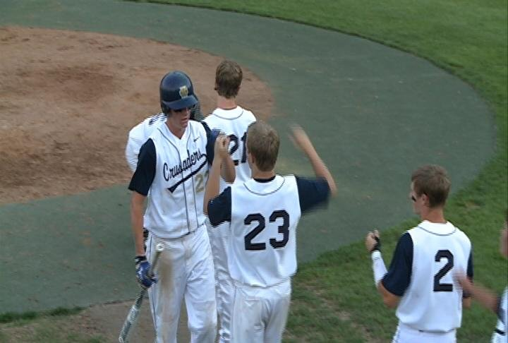 Kyle Heaton celebrates with teammates after scoring a run in Heelan's 7-5 victory.