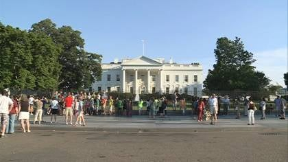 Folks gather in front of the White House.