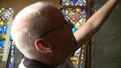 Jim Jensen points out where Trinity Lutheran's bats are hiding: the bell tower.