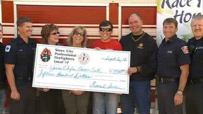 Members of Sioux City Professional Firefighters Union present a check Thursday to the June E. Nylen Cancer Center