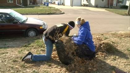Gehlen Catholic students stuff leaves into bags after raking as part of community service day projects.