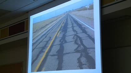 A slide showing a road with several repairs.