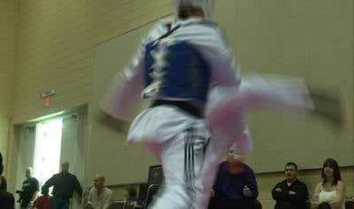 Taekwondo fighter performs roundhouse kick on opponent.