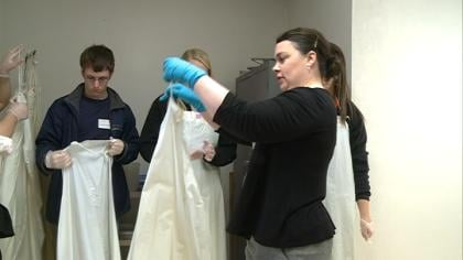 High school students put on aprons in Briar Cliff University cadaver lab.