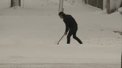 Sioux City resident clearing sidewalk after late winter snow storm.