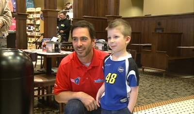 NASCAR star Jimmie Johnson poses with child at Blue Bunny Ice Cream Parlor in Le Mars, Iowa.