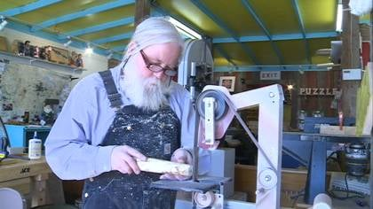 Leonard Olson sands the eye-hole end of a kaleidoscope in the making in his Pomeroy, Iowa shop